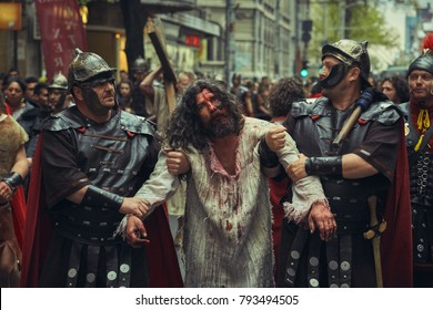 Bucharest, Romania - April 15, 2014: Scene with suffering fatigued Jesus Christ carried by Roman soldiers during the Way of the Cross reenactment.