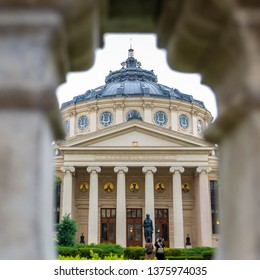 Bucharest, Romania - April 17, 2019: Romanian Athenaeum (Ateneul Roman) as seen through a crenel on the outside fence. Landmark and concert hall in the center of Bucharest, Romanian capital city.