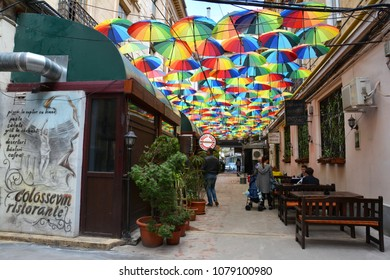 BUCHAREST, ROMANIA - APRIL 22, 2018. Rainbow umbrellas roof street in Victory Passage , Bucharest, Romania. Colloseum Restaurant.