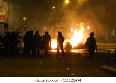 BUCHAREST, ROMANIA - August 10, 2018: Riot police spray teargas while scuffling with protesters outside the government headquarters, in Bucharest, Romania, Friday, Aug. 10, 2018.