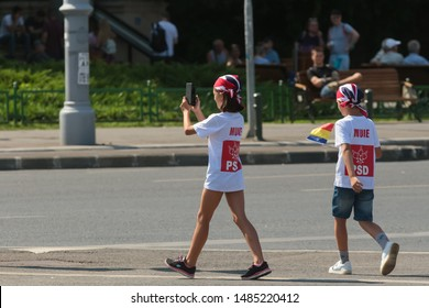 """Bucharest, Romania - August 10, 2019: Two children wearing t-shirts with the inscription """"Muie PSD"""" (suck it PSD) are seen at """"10 August rally"""" against the ruling Social Democratic Party, in Bucharest"""
