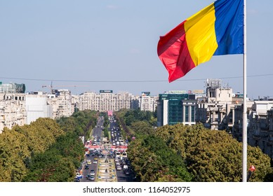 Bucharest, Romania - August 14, 2018. A Romanian flag with Unirii Boulevard at the background.