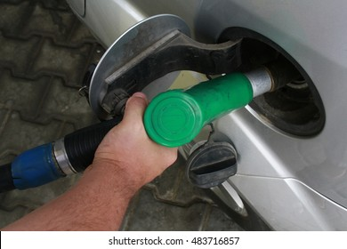 BUCHAREST, ROMANIA - AUGUST 25, 2015: Pumping gas at gas pump. Closeup of man pumping gasoline fuel in car at gas station.