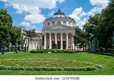 BUCHAREST, ROMANIA - CIRCA JUNE 2016: Unidentified people walk past the Romanian Athenaeum and its gardens