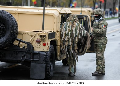 Bucharest, Romania - December 01, 2019: Gillie suit soldiers enters a Romanian Army High Mobility Multipurpose Wheeled Vehicle (HMMWV, colloquial Humvee)