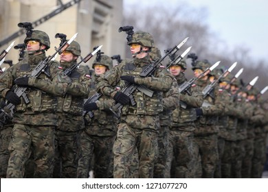 Bucharest, Romania - December 1, 2018: Polish soldiers with cameras on helmets and armed with Beryl assault rifles (holographic sights, vertical foregrips) at the Romanian National Day military parade