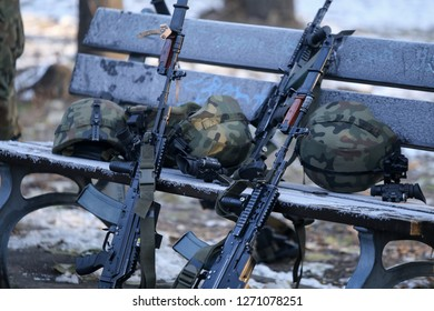 Bucharest, Romania - December 1, 2018: Polish Beryl 5.56×45mm NATO assault rifles with holographic sights, vertical foregrips and bayonets lay on the ground with other army objects