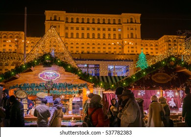 BUCHAREST, ROMANIA - DECEMBER 17, 2016: People Gather At The Christmas Market Downtown Bucharest City At Night In front of the Parliament House, the second largest building in the world