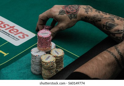 Bucharest, Romania, December 19, 2015: A gambler with tattooed hands arranges chips in a poker festival organized in Bucharest.