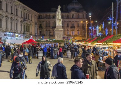 BUCHAREST, ROMANIA - DECEMBER 23, 2014: Christmas market in Bucharest during night with lots of people eating and buying gifts for the loved ones