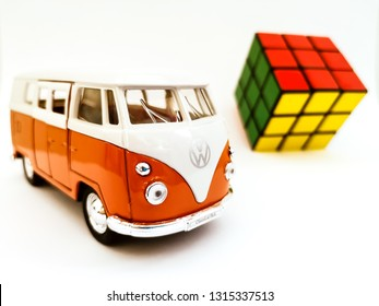 BUCHAREST, ROMANIA - FEBRUARY, 10, 2019: Eighties Symbols. Toy car illustrating Volkswagen T1 known as the hippie microbus and the Rubik's Cube. Both are symbols of the '80s.