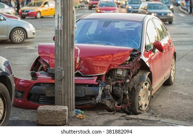 Bucharest, Romania - February 15, 2016: Red vehicle wrecked in horrific car accident in Unirii Square intersection, dragged near sidewalk
