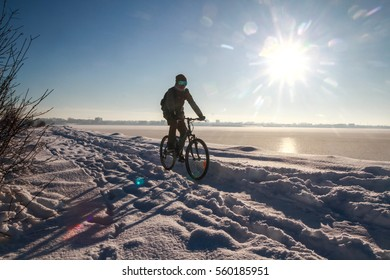 Bucharest, Romania, January 1, 2015: A man rides his bike on the edge of a lake in Bucharest, during a cold winter day.