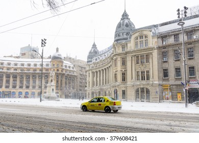 Bucharest, Romania - January 17: University Square on January 17, 2016 in Bucharest, Romania. Bucharest downtown after massive snowing, University Square, city center neighborhood, taxi car street.