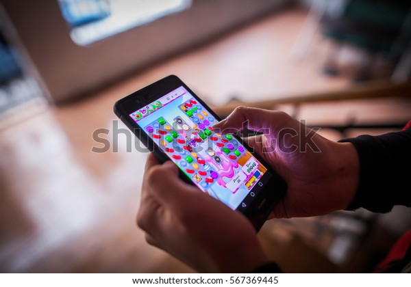 BUCHAREST, ROMANIA - January 25, 2017: Close up illustrative editorial shot of a person's hands, holding a smartphone and playing Candy Crush Saga game.