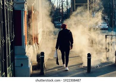 Bucharest, Romania, January 6, 2021: person walking on the sidewalk amongst bright, back lit sewage vapors on a sunny winter day.