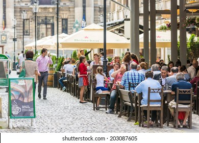BUCHAREST, ROMANIA - JULY 04, 2014: Tourists Having Lunch At Outdoor Restaurant Downtown Lipscani Street. Lipscani is one of the most busiest streets of central Bucharest.