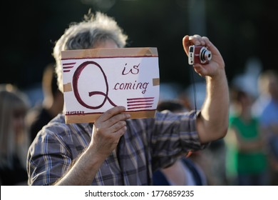 Bucharest / Romania - July 15, 2020: A man takes part at a protest and displays a Qanon message on a cardboard.