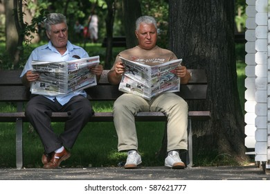 Bucharest, Romania, July 20, 2009: Two old men are reading newspaper on a bench in a park.