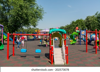 BUCHAREST, ROMANIA - JUNE 08, 2014: Children Playground In Youths Public Park (Tineretului Park) On Summer Day. Created in 1965 is one of the largest fun parks in south Bucharest.