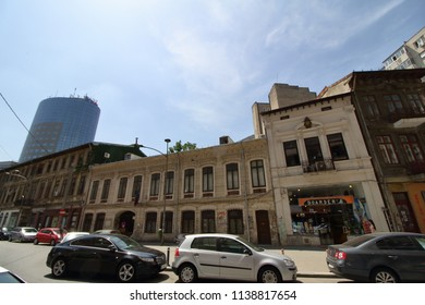 Bucharest, Romania - June 11, 2018: A modern high-rise building in contrast to some old buildings located on a street in downtown Bucharest, Romania.