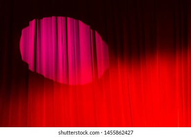 Bucharest, Romania - June 13, 2019: A lowered red curtain on which a round spot light falls is see on a theatre stage before a political event in Bucharest.