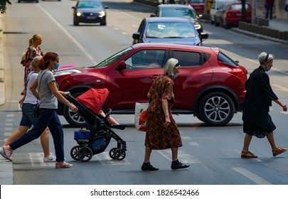 Bucharest, Romania - June 30, 2020: Pedestrians cross the street on Regina Elisabeta Boulevard in Bucharest, Romania.