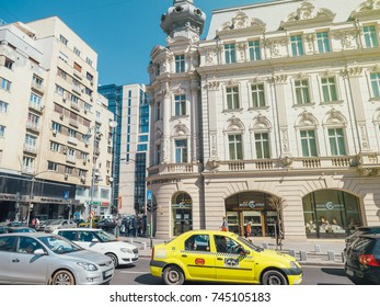 BUCHAREST, ROMANIA - MAR 31 2016: 19th century Grand Hotel Continental and mix of communist and modern buildings in downtown Bucharest Victoria road in peak hours