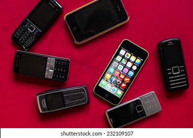BUCHAREST, ROMANIA - MARCH 17, 2014: Photo of iphone versus old Nokia phones on a red background showing the evolution of mobile phones