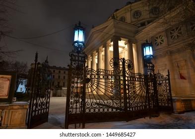 Bucharest, Romania - March 18, 2018:   Romanian Athenaeum concert hall, landmark of Romanian capital city illuminated in the evening. Side view through metallic gate.