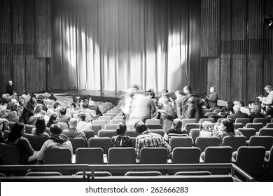BUCHAREST, ROMANIA - MARCH 22, 2015: Black And White Photo Of People Taking Their Seats In Theater Inside.
