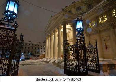 Bucharest, Romania - March 23, 2018:   Romanian Athenaeum concert hall, landmark of Romanian capital city illuminated in the evening. Early snowy springtime.