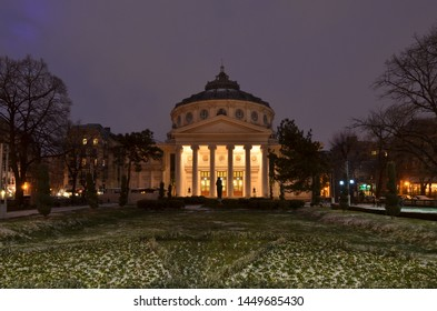 Bucharest, Romania - March 23, 2018:   Romanian Athenaeum concert hall, landmark of Romanian capital city illuminated in the evening. Early spring with snow.