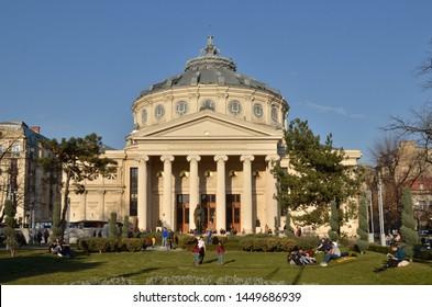 "Bucharest, Romania - March 23, 2018:   People enjoy time besides Romanian Athenaeum concert hall, home of ""George Enescu"" Philharmonic, landmark of Bucharest city."