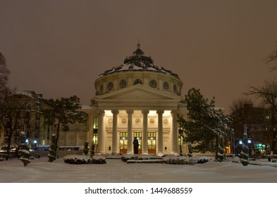 Bucharest, Romania - March 23, 2018:   Romanian Athenaeum concert hall, landmark of Romanian capital city illuminated in the evening, on cold snowy early spring.