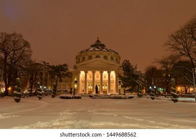 Bucharest, Romania - March 23, 2018:   Romanian Athenaeum concert hall, landmark of Romanian capital city illuminated at evening. Early spring with snow.