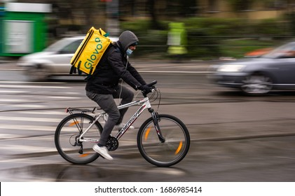 Bucharest, Romania - March 23, 2020: A Glovo food delivery courier wearing mask on a bike. Restaurants are closed and only deliveries are allowed during the state of emergency due to coronavirus.