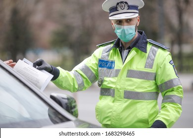 Bucharest, Romania - March 25, 2020: Romanian road police officer pulls over a car to check for the driver's identity papers.