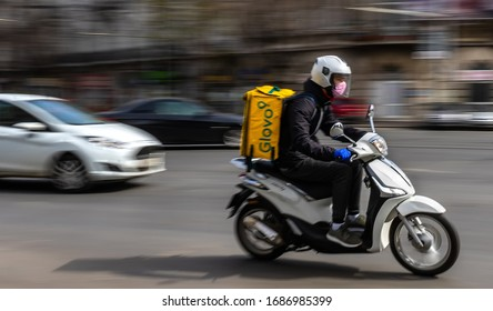 Bucharest, Romania - March 26, 2020: A Glovo food delivery courier wearing mask on a scooter. Restaurants are closed and only deliveries are allowed during the state of emergency due to coronavirus