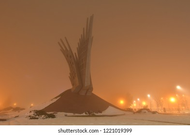 Bucharest, Romania - March 6. 2018: Wings, monument dedicated to Romanian fighters from anti-communist Resistance 1945 - 1989. Author Mihai Buculei.  Mysterious misty night atmosphere. Angle view.