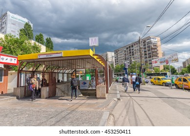 Bucharest, Romania - May 07, 2016: People crossing Dristor 1 subway station entrance in a cloudy spring day