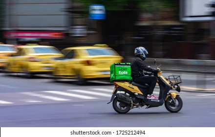 Bucharest, Romania - May 07, 2020: Uber Eats food delivery courier on a scooter in high speed. Restaurants are closed and only deliveries are allowed during the state of emergency due to coronavirus