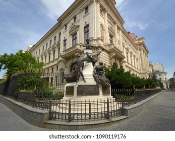 Bucharest / Romania, May 14, 2018: Monument to Eugeniu Carada (1836-1910), founder of The National Bank of Romania and the head office of the National Bank of Romania, as seen from Lipscani Street
