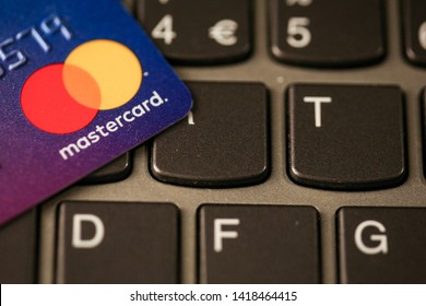Bucharest, Romania - May 14, 2019: Macro image with the details of a Mastercard plastic credit card with the Mastercard logo on a laptop keyboard - online payment.