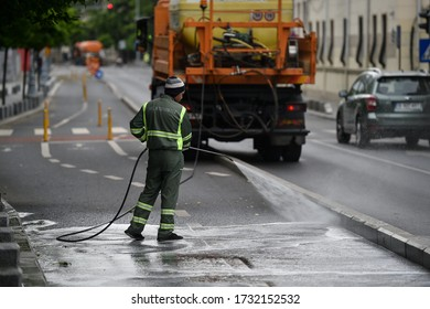 BUCHAREST, ROMANIA - MAY 15, 2020: Public janitor deep cleaning the sidewalk and cycling lane with high pressure disinfectant solution in times of corona virus pandemic in a lockdown Bucharest, Romani