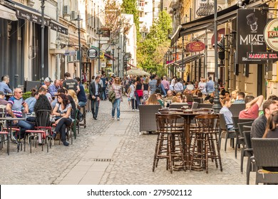 BUCHAREST, ROMANIA - MAY 18, 2015: Tourists Visiting And Having Lunch At Outdoor Restaurant Cafe Downtown Lipscani Street, one of the most busiest streets of central Bucharest.