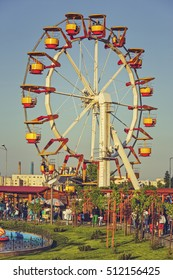 Bucharest, Romania - May 19, 2014: People have fun, relax or enjoy a ride in a giant colorful ferris wheel in Tineretului Park, a large amusement public park created in 1965 in southern Bucharest.