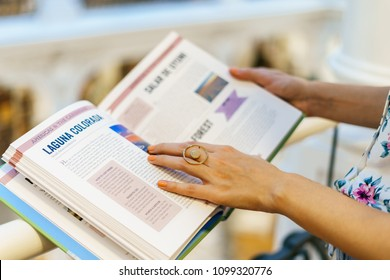 BUCHAREST, ROMANIA - MAY 27, 2018: Woman Wearing Minimalist Contemporary Jewelry Reading Book In Library Store