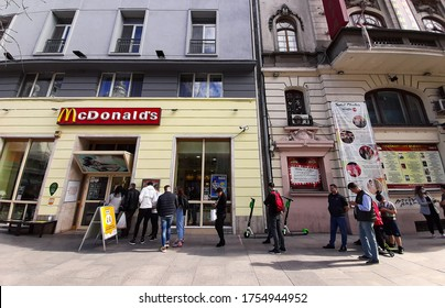 Bucharest, Romania - May 27, 2020: People queuing to buy food from from McDonalds are not allowed to eat in the restaurant due to the rules of the state of emergency due to coronavirus.