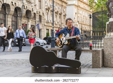 BUCHAREST, ROMANIA - MAY 29, 2015: Street musician playing a quitar to earn some money, in the oldtown of Bucharest, Romania